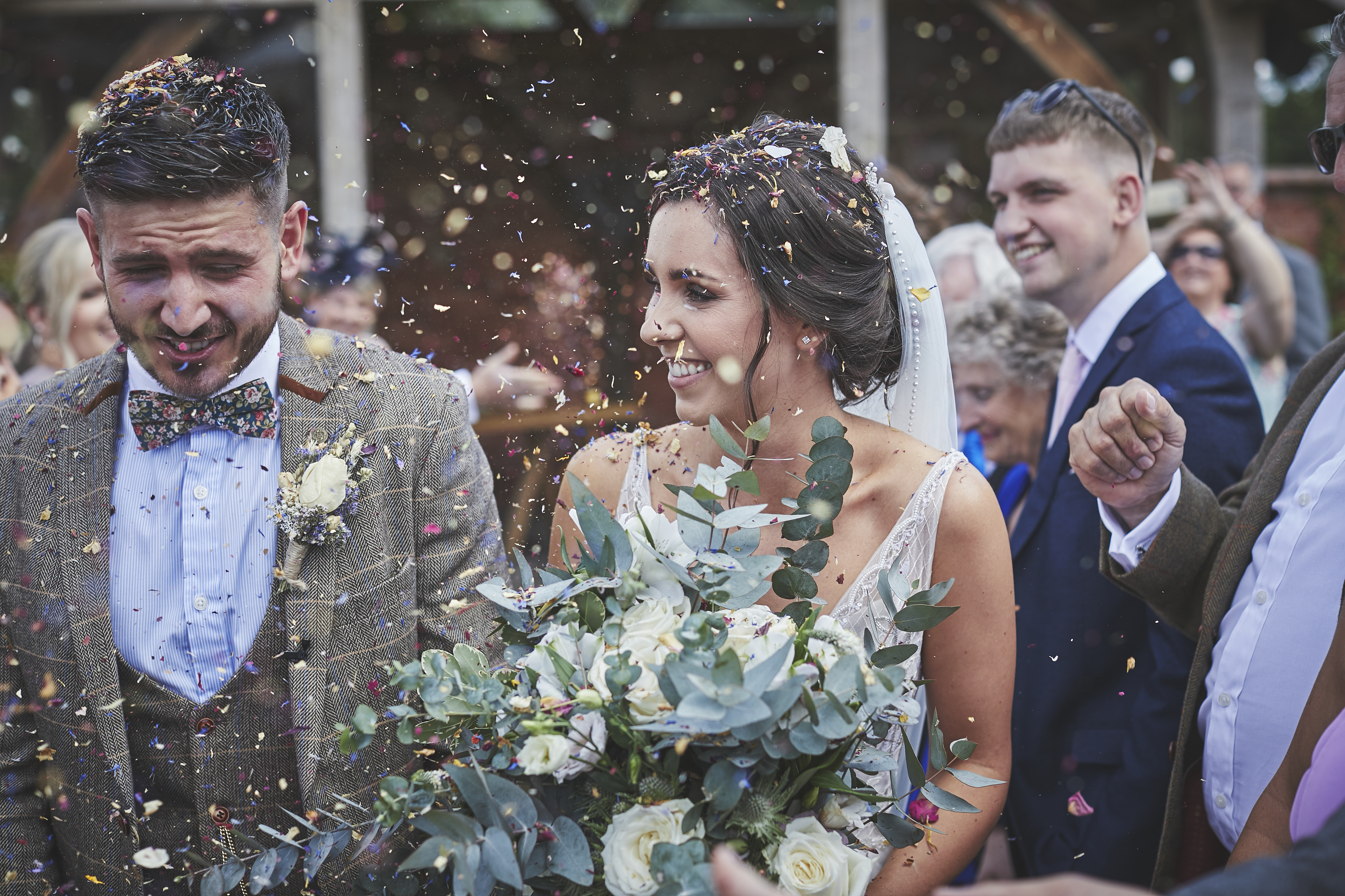 Bride and Groom engulfed in flower confetti in front of the arbour at Upton Barn