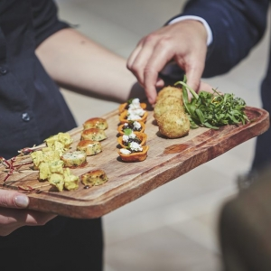Close up of Canapes served by waitress on a wooden board