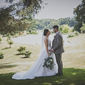 Bride and Groom stood in front of Upton Barn Lake in full sun