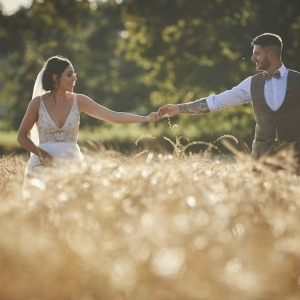 Bride and Groom walk hand in hand waist deep in corn field