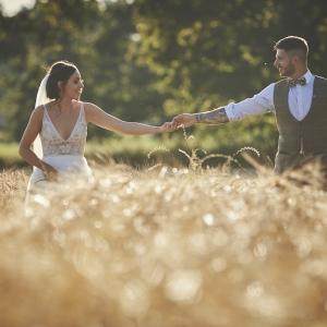 Bride and Groom walk hand in hand waist deep in corn field