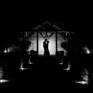 Black and white silhouette of Bride and Groom embracing in the Arbour at Upton Barn & Walled Garden