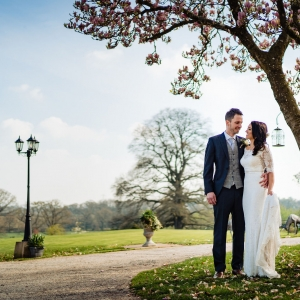 Bride and Groom embrance under a tree at Upton Barn & Walled Garden