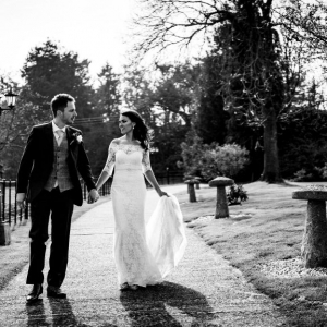 Bride and Groom walk down the entrance path hand in hand at Upton Barn & Walled Garden