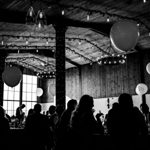 Black and White photo of guests enjoying a Wedding Breakfast in The Stable Barn at Upton Barn & Walled Garden