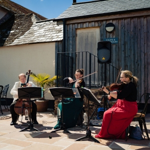 String trio play on the patio of Upton Barns Walled Garden