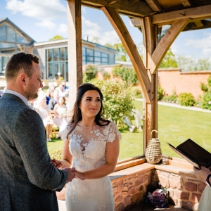 Bride and Groom exchange vows in the arbour at Upton Barn
