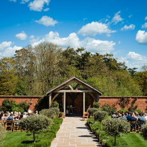 Bride and Groom seat to sign the registrar in the Arbour at Upton Barn with guest seated in the Walled Garden