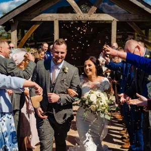 Bride and Groom showered in confetti in the aisle in front of the arbour at Upton Barn