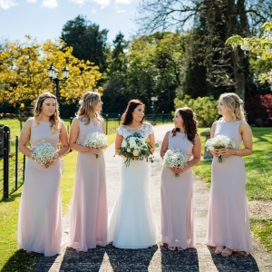 Bride and her maids with bouquets stand in the entrance to Upton Barn
