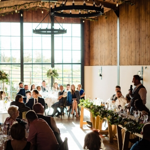 Groom standes to give a speech in the Stable Bar in front of wedding guests