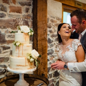 Bride and Groom cut their wedding cake on top of Oak Barrel at Upton Barn