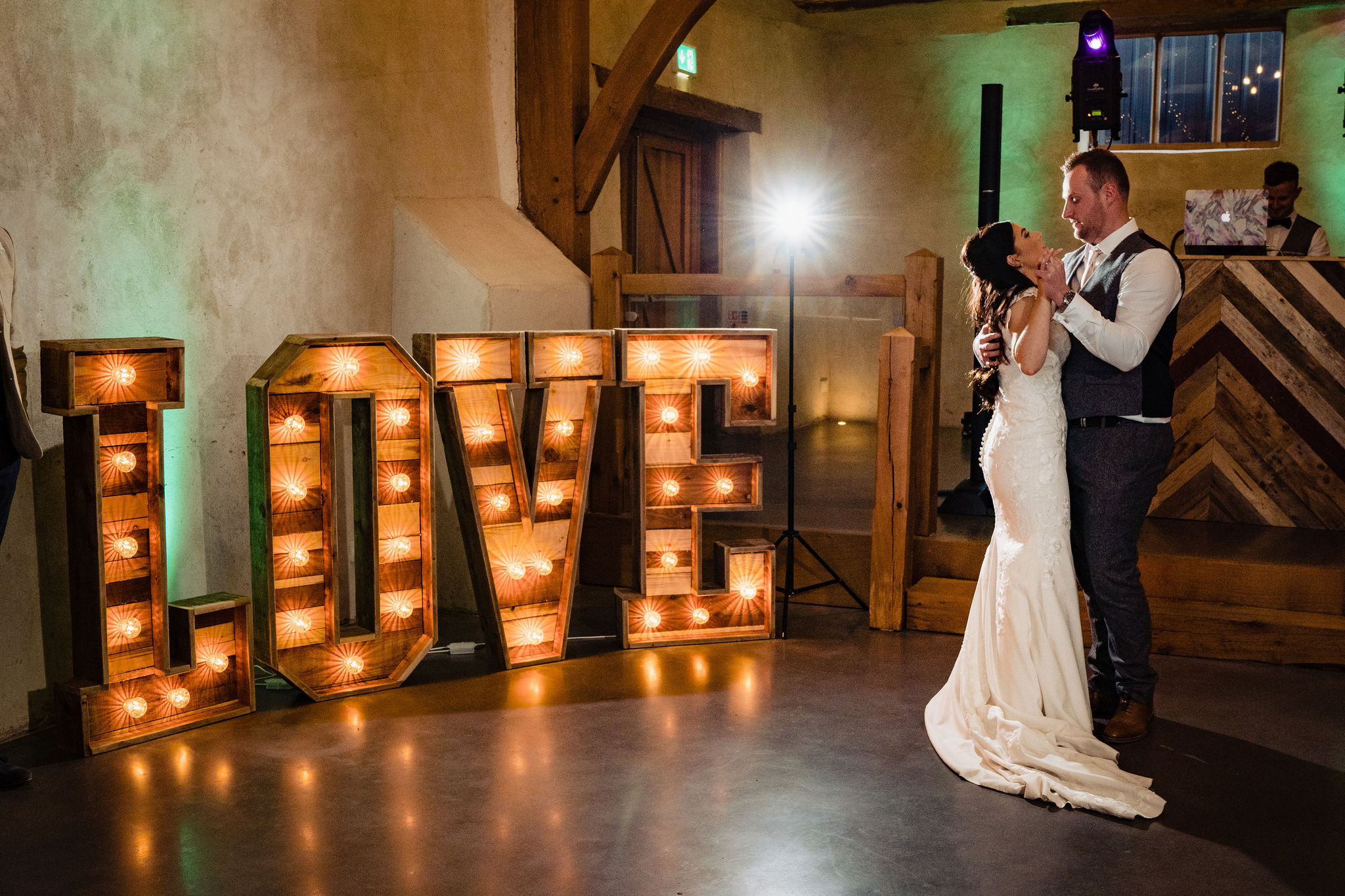Bride and Groom dance by large Love letter lights in front of dj in the Cider Barn at Upton Barn Wedding Venue