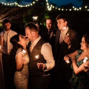Bride and Groom embrace surrounded by guests all with Sparkler at night