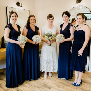Bride and her maids pose in the Tack Room with thier bouquets