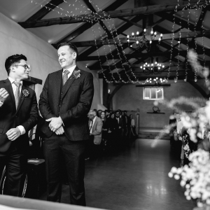 Groom and Bestman share a joke at the end of the Cider Barn aisle while they await the bride