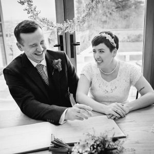 Bride and groom share wide grins while signing the wedding register