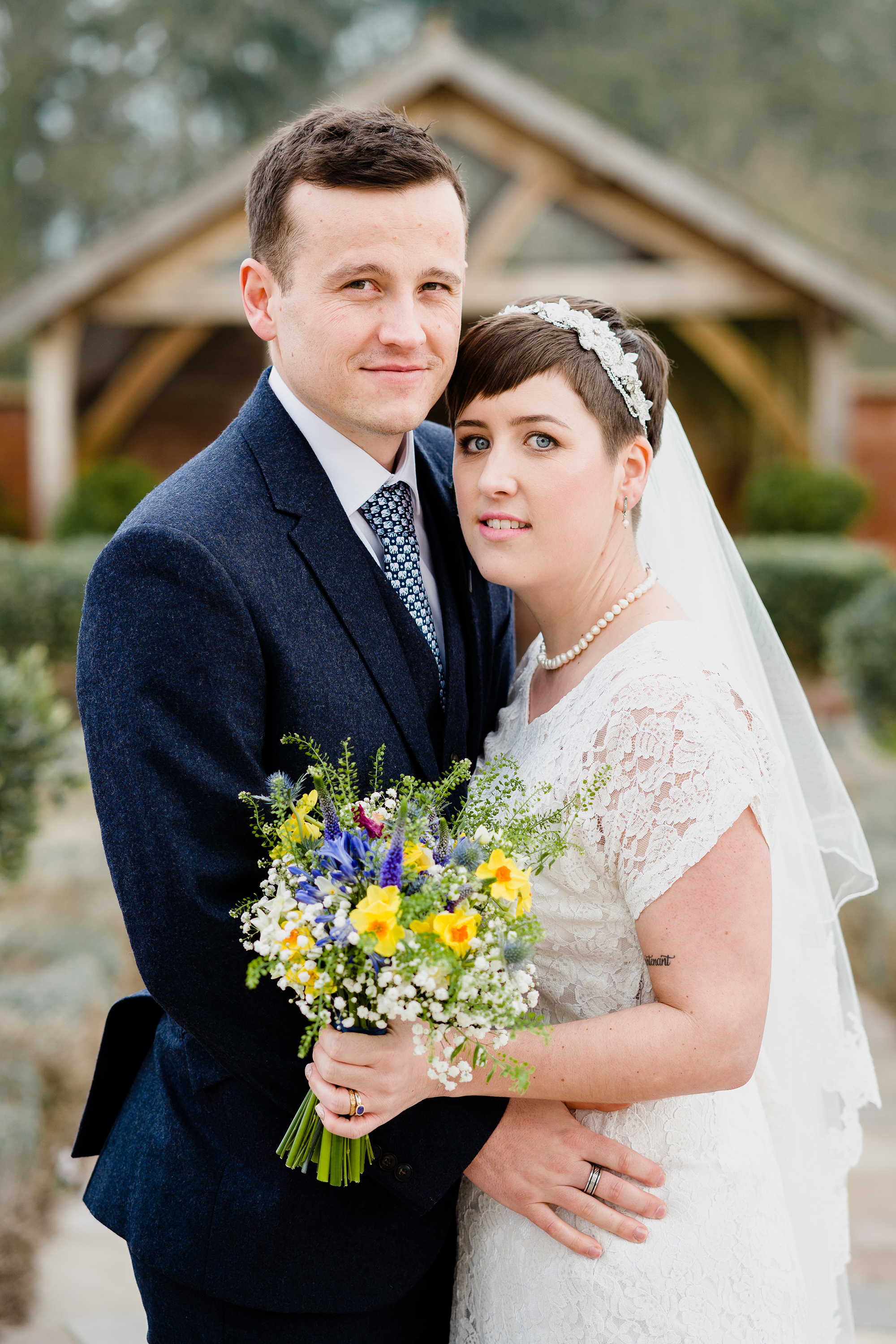 Bride and Groom pose infront of The Arbour at Upton Barn and Walled Garden