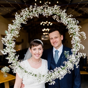 Bride and Groom pose looking through a circular wreath of babys breath flowers
