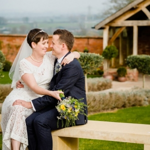 Bride sits on Grooms lap and looks in his eyes in the Walled Garden at Upton Barn
