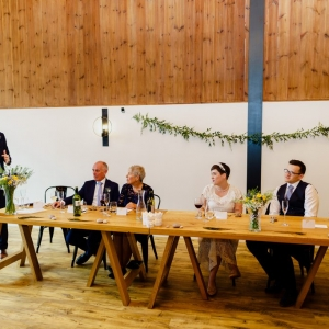 Guests at the Top Table look on attentively to the Best Man giving his speech