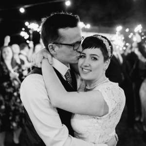 Groom kisses bride while guests wave sparklers in the background