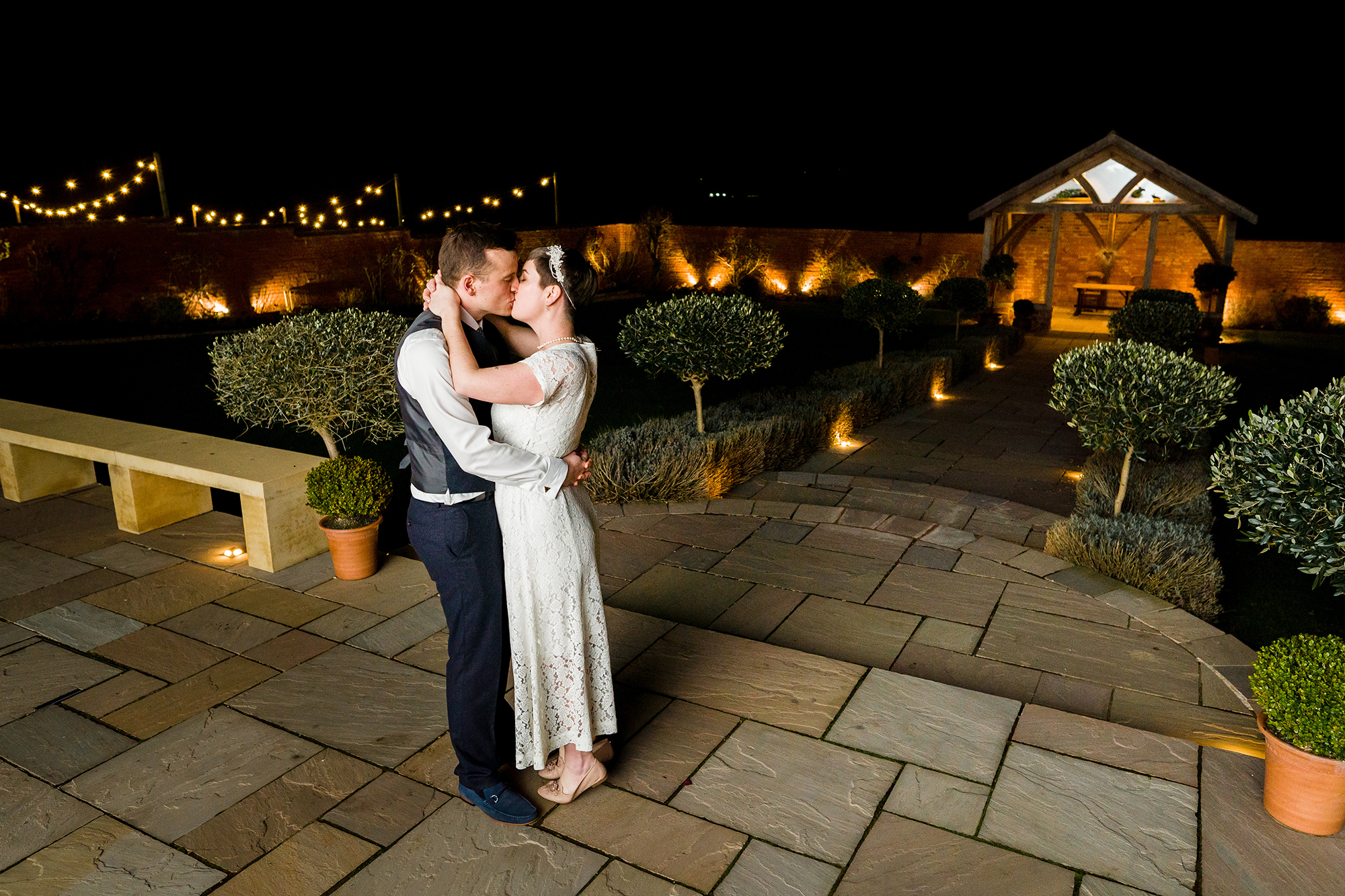 Bride and Groom kiss in romanticlly lit Walled Garden at night