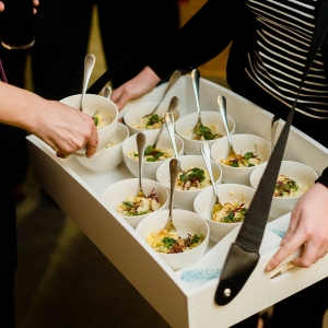 Waiting staff serve up bowl food from a tray