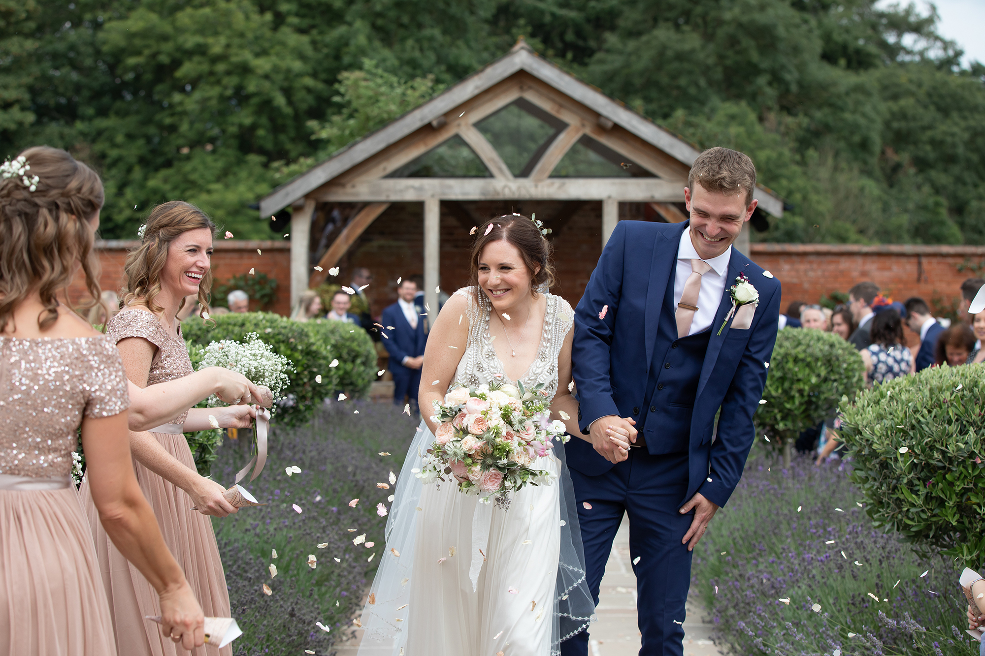 Bride and Groom shy away from confetti thrown by the bridesmaids
