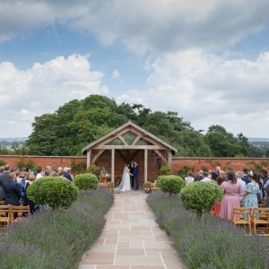 Bride and Groom exchange vows in the Arbour of the Walled garden in front of their guests