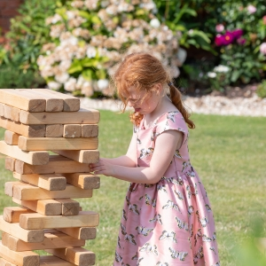 Yound girl guest concentrates while playing giant Jenga game in the garden
