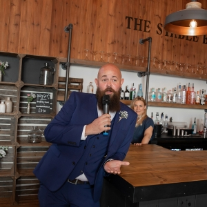 A groomsman delivers a speech in a mic proped at the end of The Stable Bar