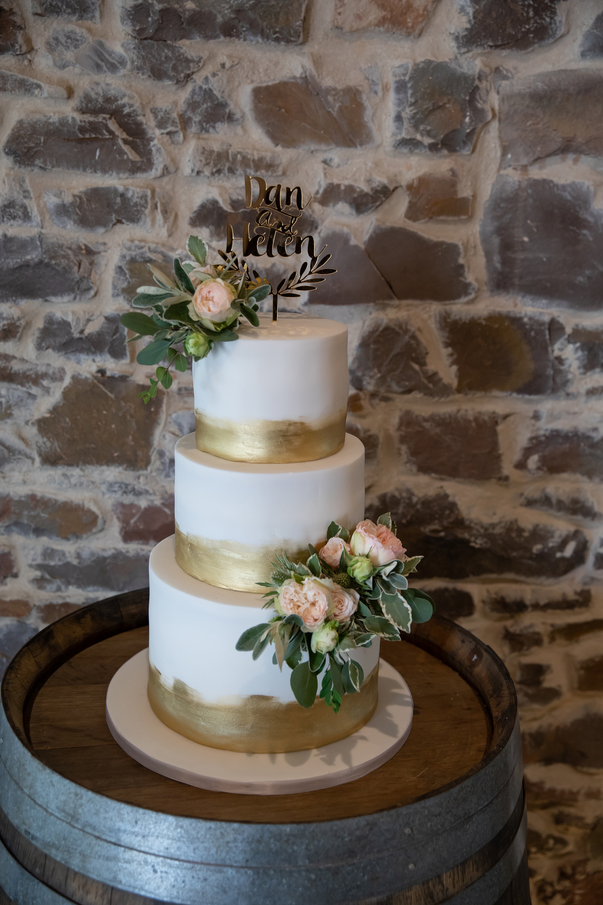 Gold and ivory brush work wedding cake with gold text name topper decorated with fresh flowers