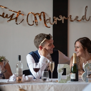 """Bride and Groom smile at each other while sat at the dinner table with """"Just Married"""" sign behind them"""