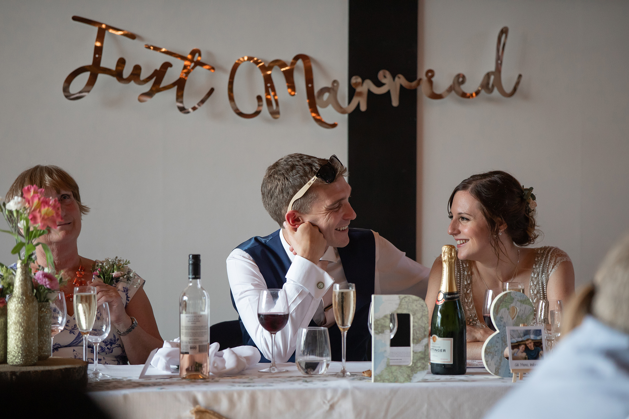 "Bride and Groom smile at each other while sat at the dinner table with ""Just Married"" sign behind them"