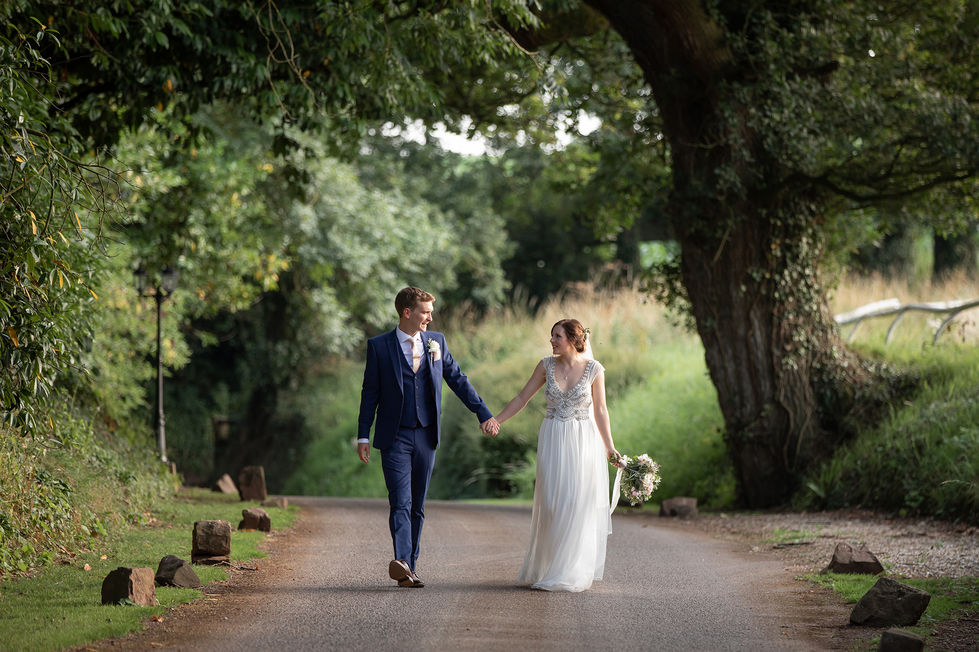 Bride and Groom walk hand in hand along the tree lined lane to Upton Barn