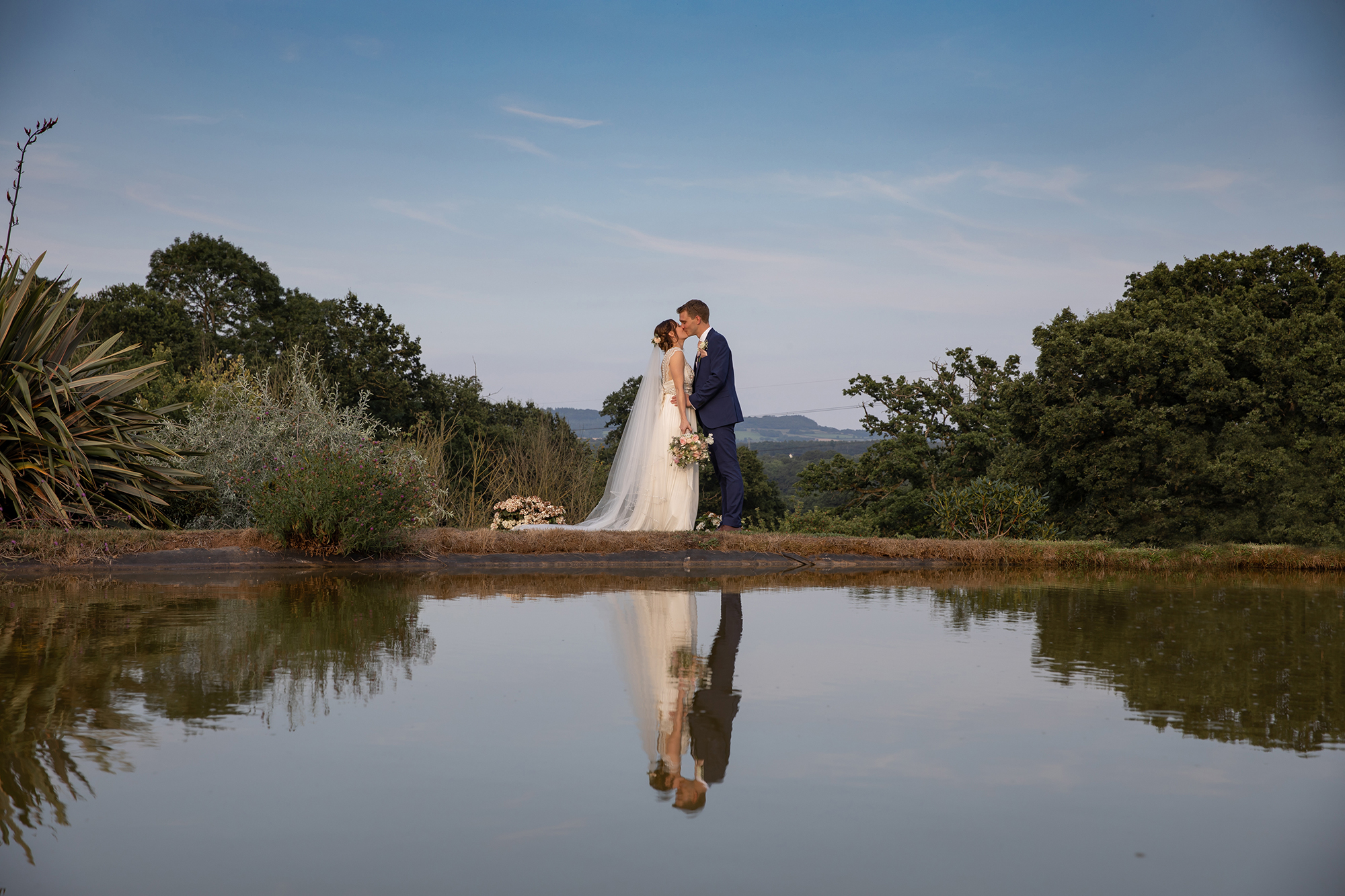 Bride and Groom kiss and embrace besides the lake and pale blue cloudless sky