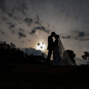 Silhouette of Bride and Groom against setting sun and high clouds