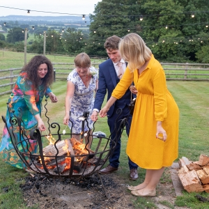 Wedding guests toast marshmellows over a fire pit at Upton Barn