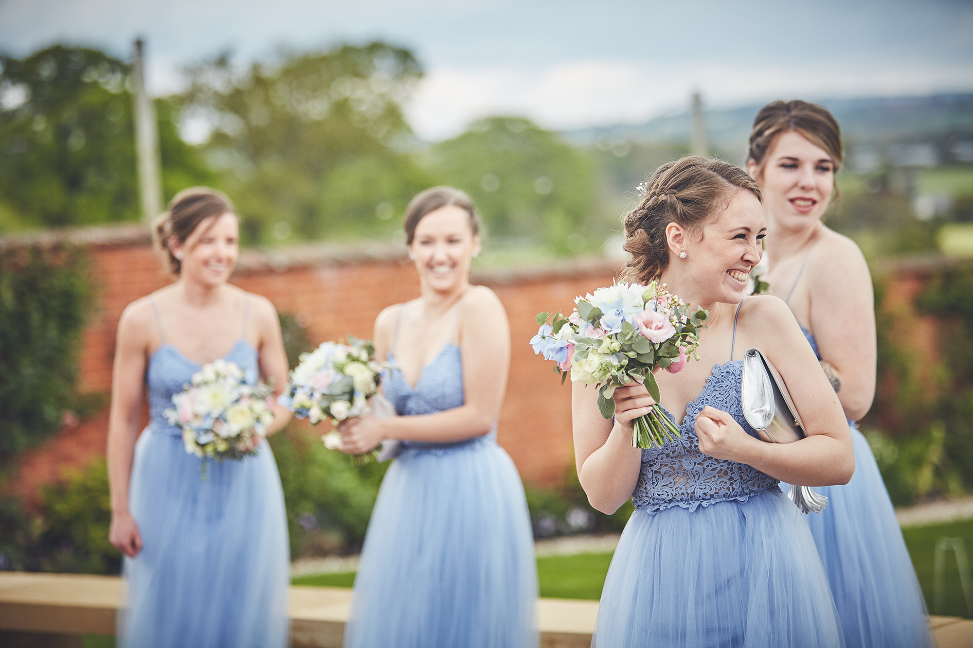 Bridesmaids dressed in blue with bouquets in the Walled Garden