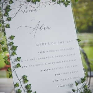 Close up of wedding Order Of The Day Sign decorated in ivy