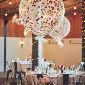 Large oversized dotty balloon floats above Wedding Breakfast tables in the Stable Barn
