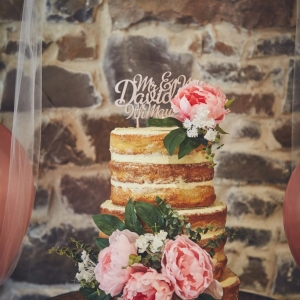 Naked sponge wedding cake with ornate date and name topper decorated with faux flowers
