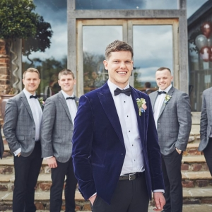 Groom with his groomsmen behind him on the steps to the Cider Barn at Upton
