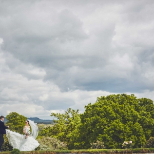 Groom holds brides dress off the ground as they walk around the lake