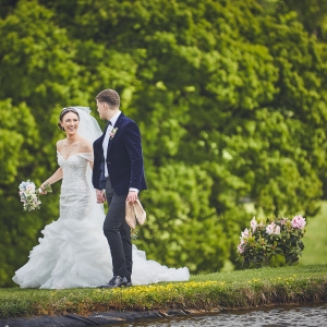Groom holds brides shies as she walks bare foot around the lake