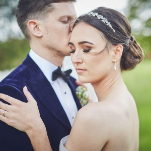 Bride closes eyes as she embraces her groom in the gardens of Upton Barn