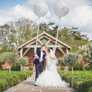 Bride and Groom hold oversized balloons with Mr & Mrs on them in the Walled Garden at Upton