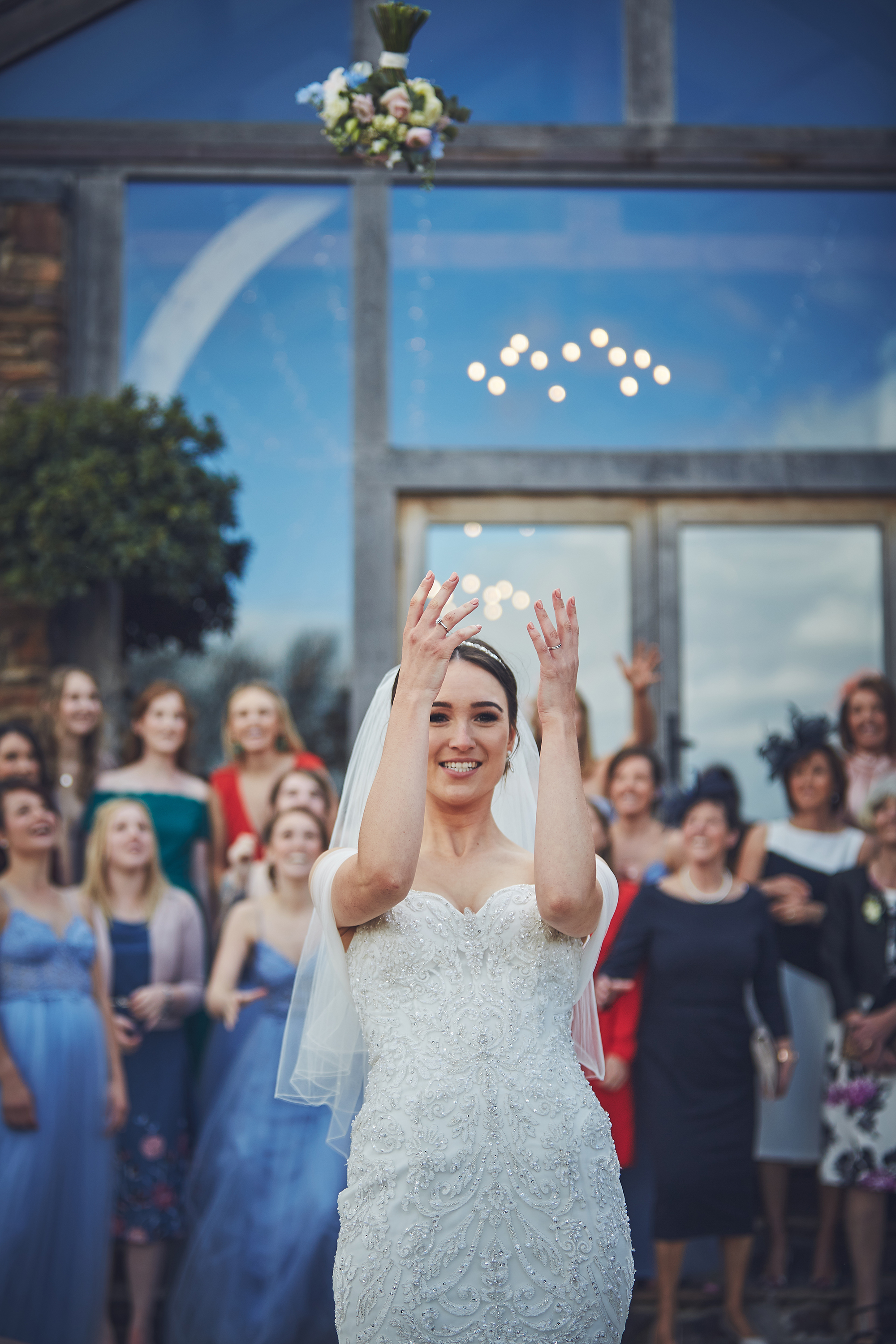 Bride throws bouquet over her head to the bridesmaids and female guests