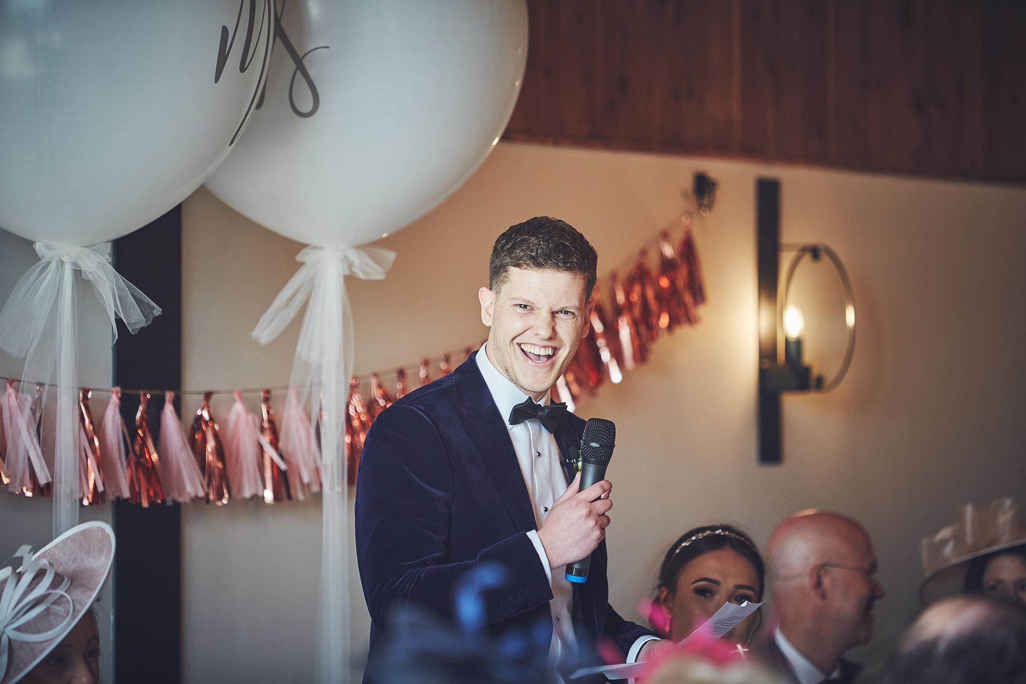 Groom gives broad smile as he delivers speech with mic in hand.